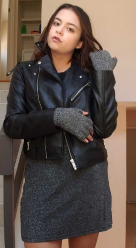 Woman wearing leather jacket, sparkly gray skirt and fingerless gloves.