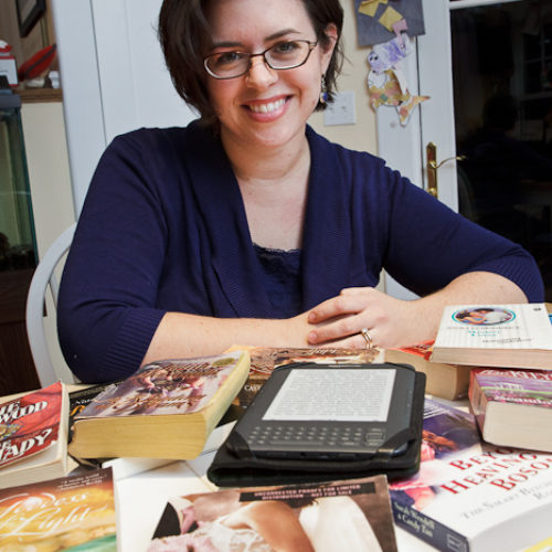 Sarah Wendell, author of the blog smartbitchestrashybooks.com,  at her home with some of her favorite romance novels and her kindle which she uses for the bulk of her reading this year.