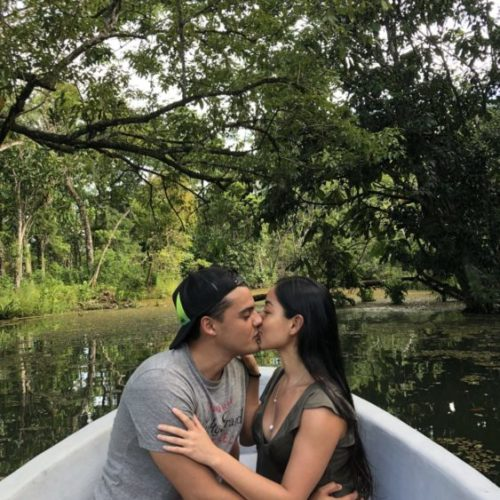 Man and woman kissing while sitting in boat