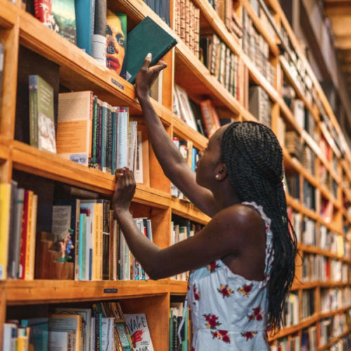woman standing in front of books